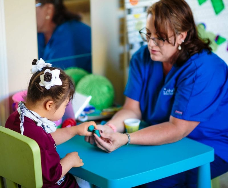 nurse with little girl playing with clay