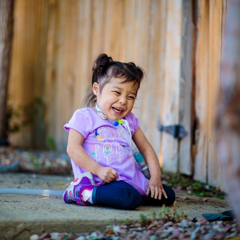 little girl sitting on sidewalk