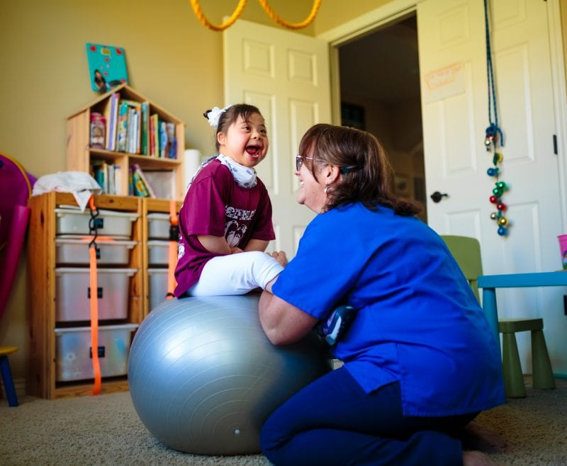 nurse with little girl on exercise ball
