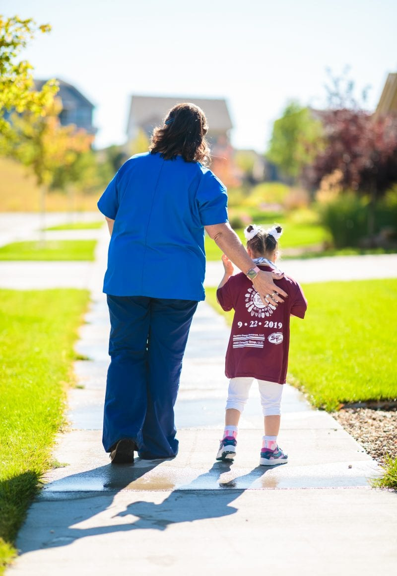 nurse walking with little girl outside