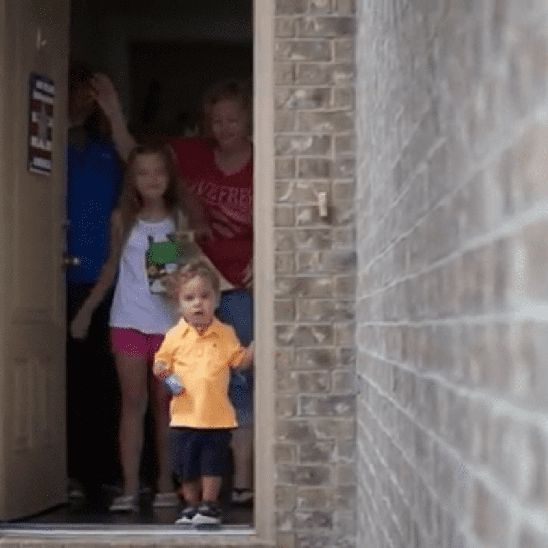 little boy and family at the front door