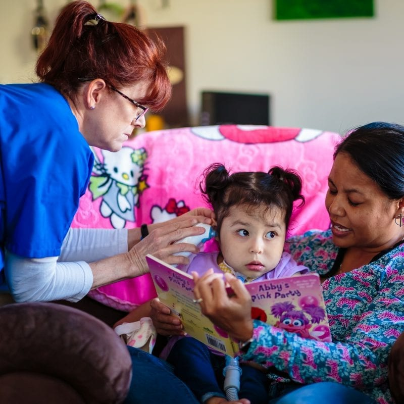 two nurses reading with little girl