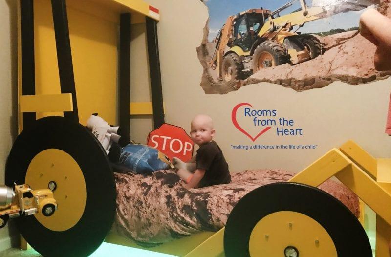 little boy in bulldozer bed